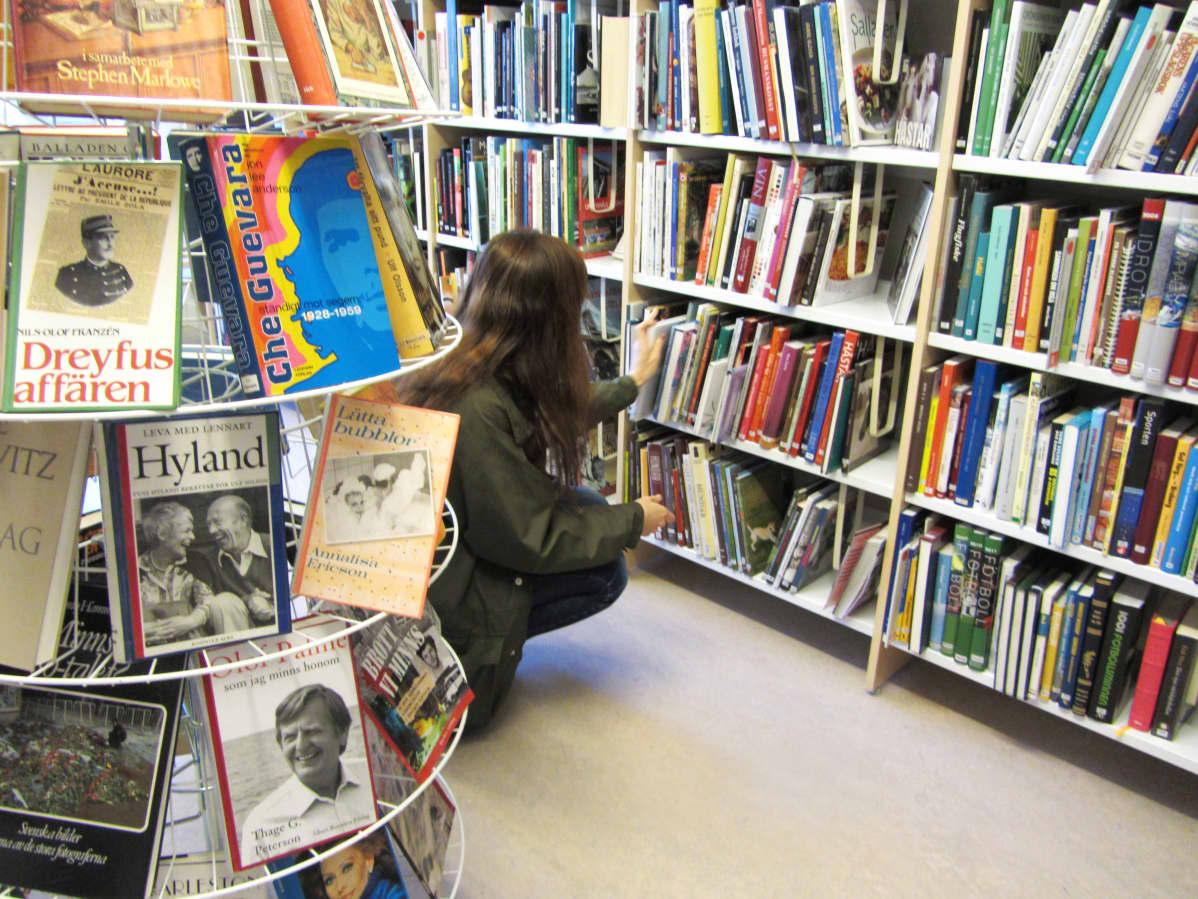 En kvinna står på huk framför en bokhylla i biblioteket och letar efter böcker