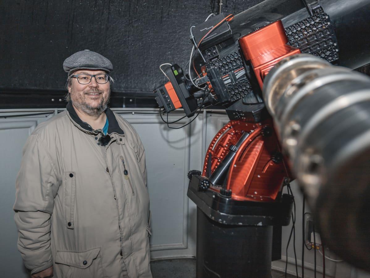 Tähtitieteen harrastaja Arto Oksanen seisoo peiliteleskoopin vierellä
