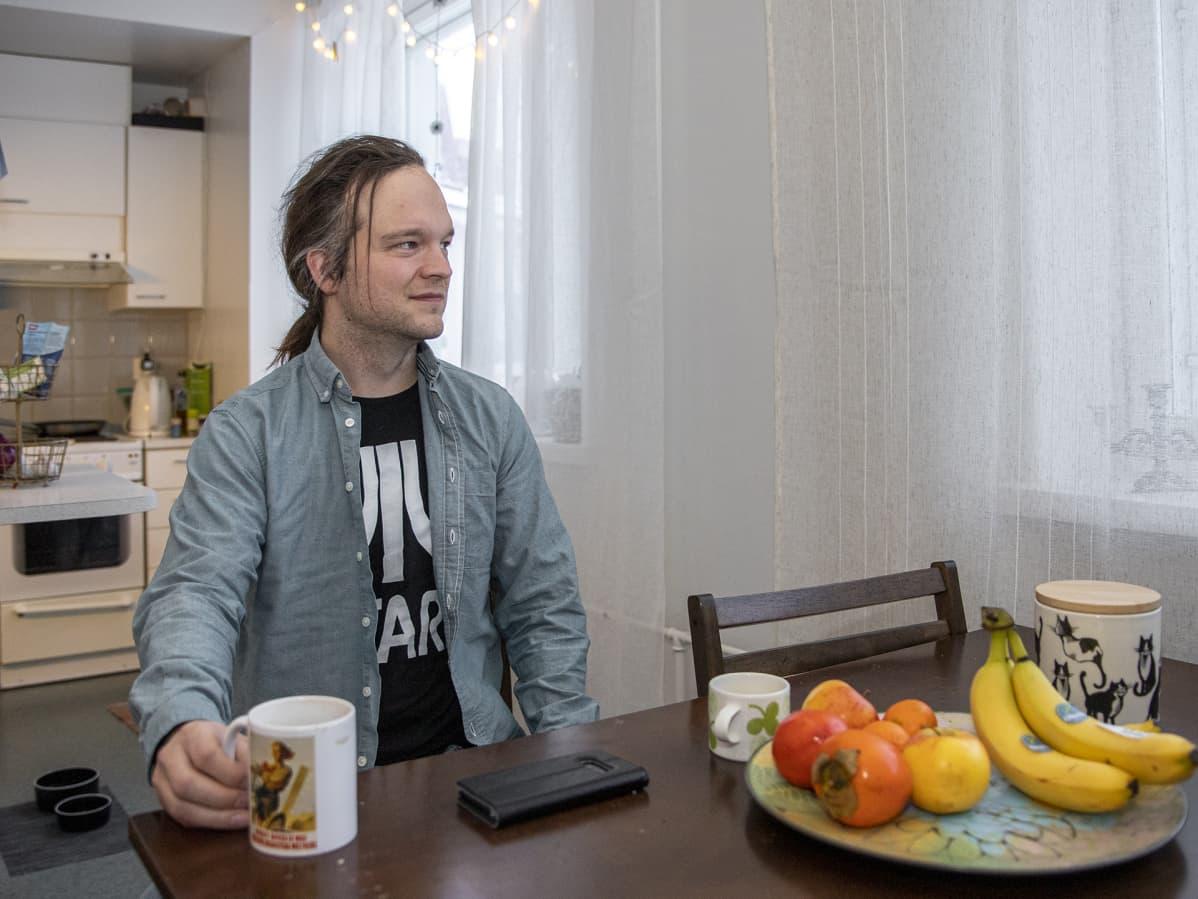 Ville Salminen istuu pöydän äärellä.