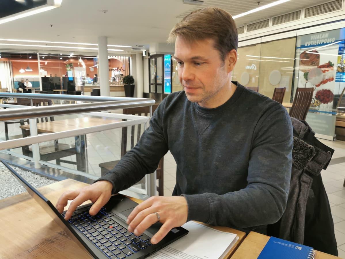 Työelämäntutkija Pasi Pyöriä tekee etätöitä kahvilassa Tullintorin kauppakeskuksen kahvilassa Tampereella