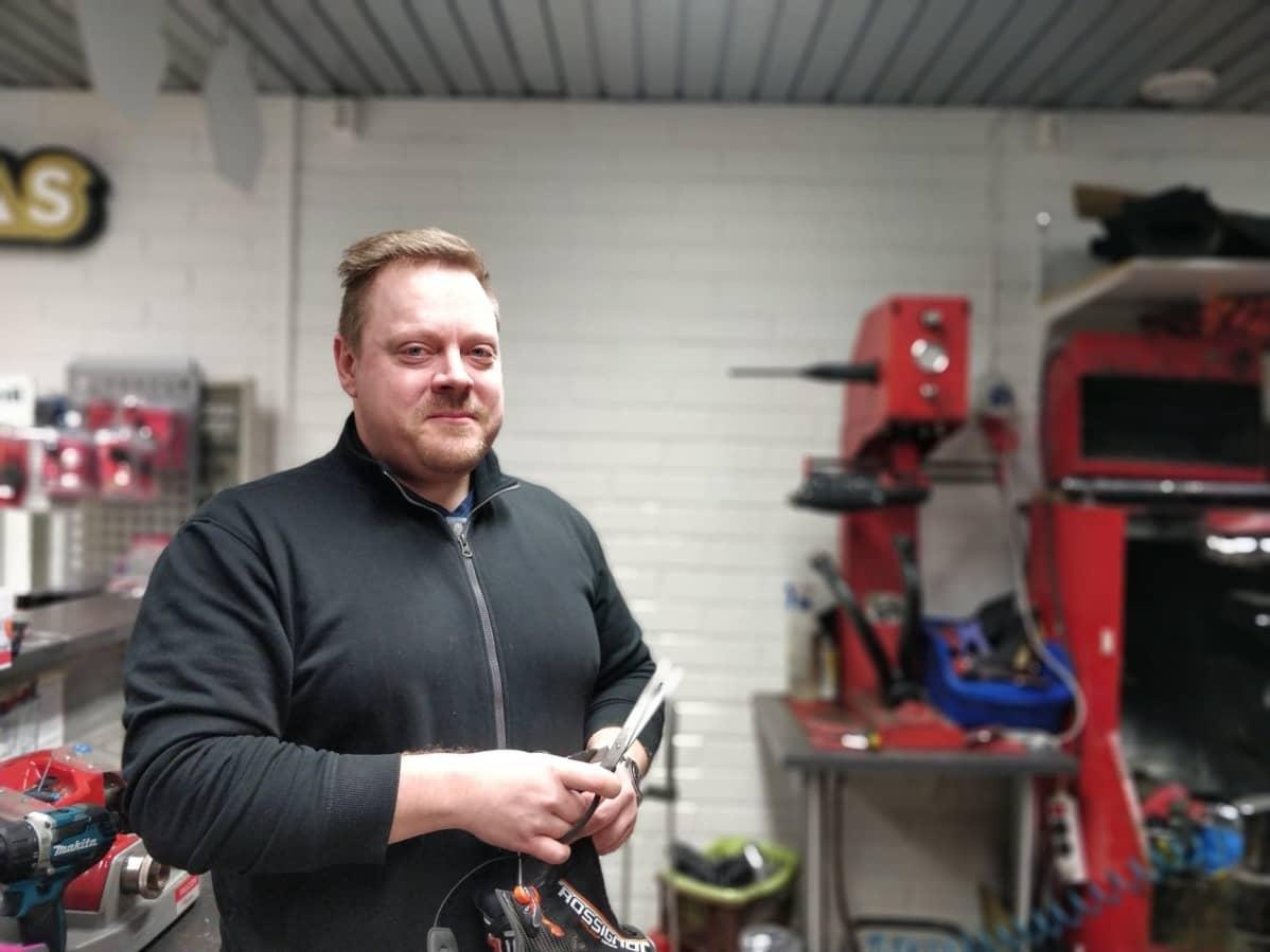 Suutari Antti Rautiainen esittelee kenkiä, joihin on laittamassa nastoja.
