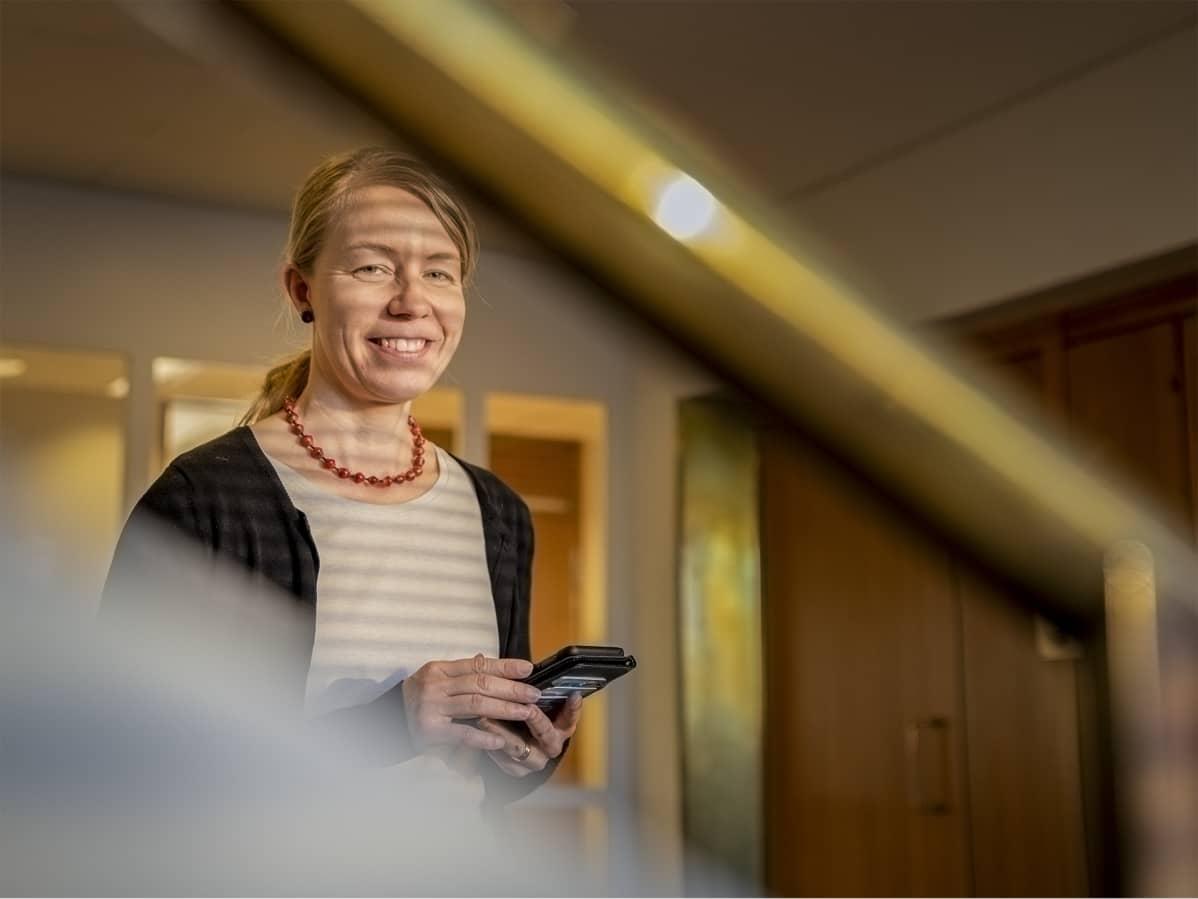 Tanja Oksa pitelee käsissään puhelinta ja hymyilee.