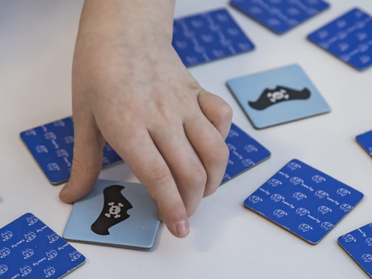 Muistipelikortteja nostetaan pöydältä.