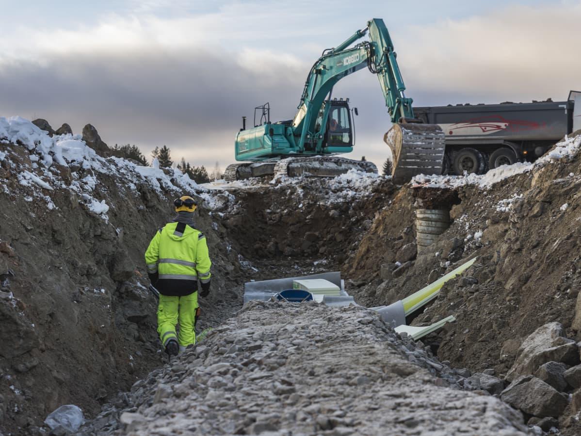 Kaivinkoneet kaivavat putkia maahan.