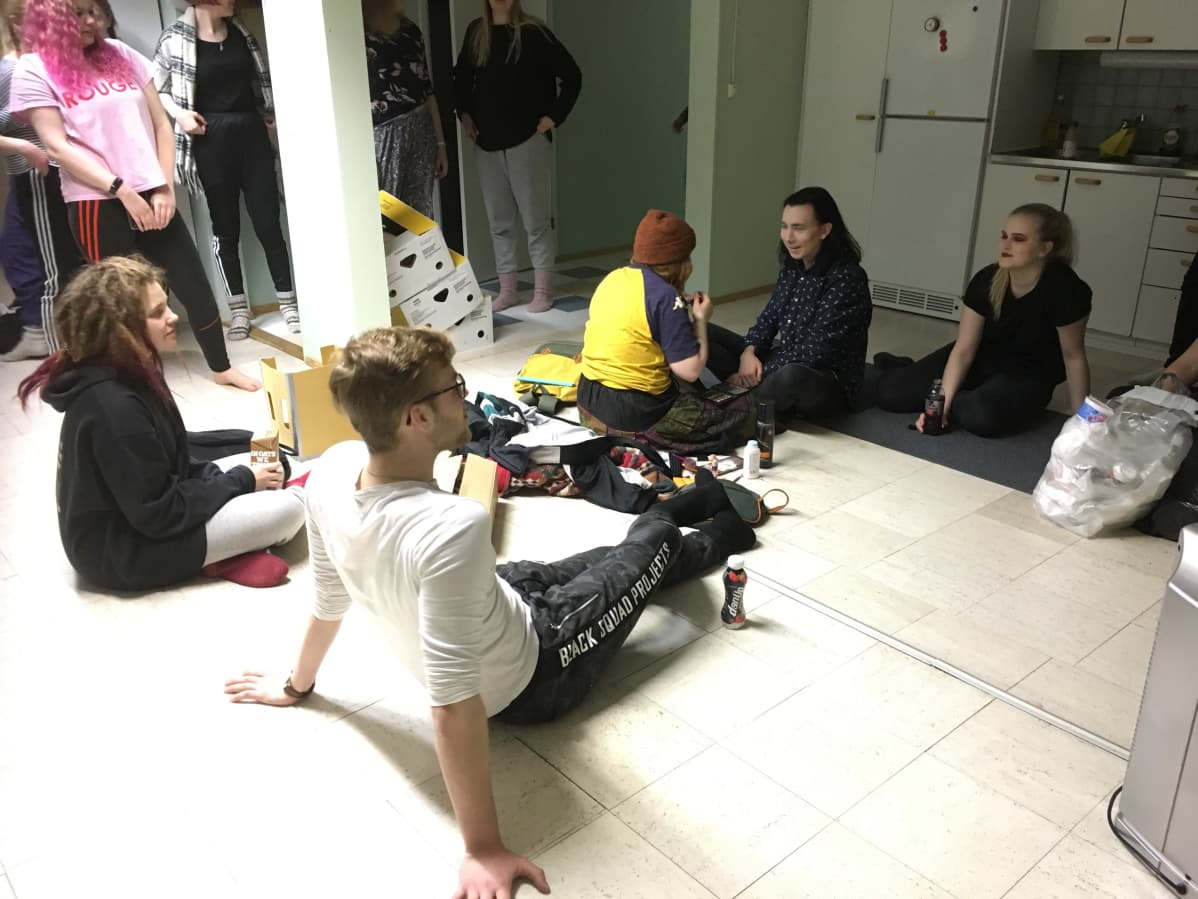 Abeja istuu lattialla