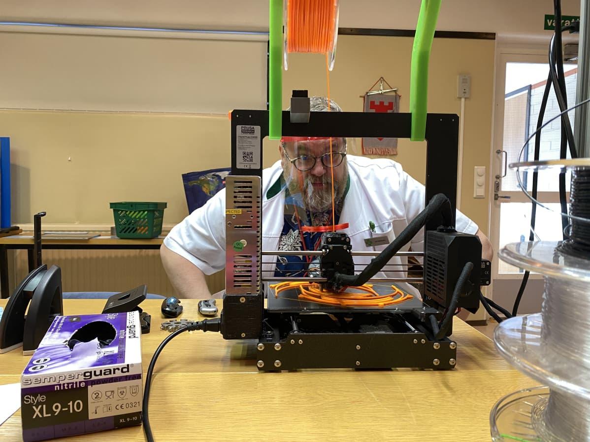 Mies tulostaa 3D-tulostimella