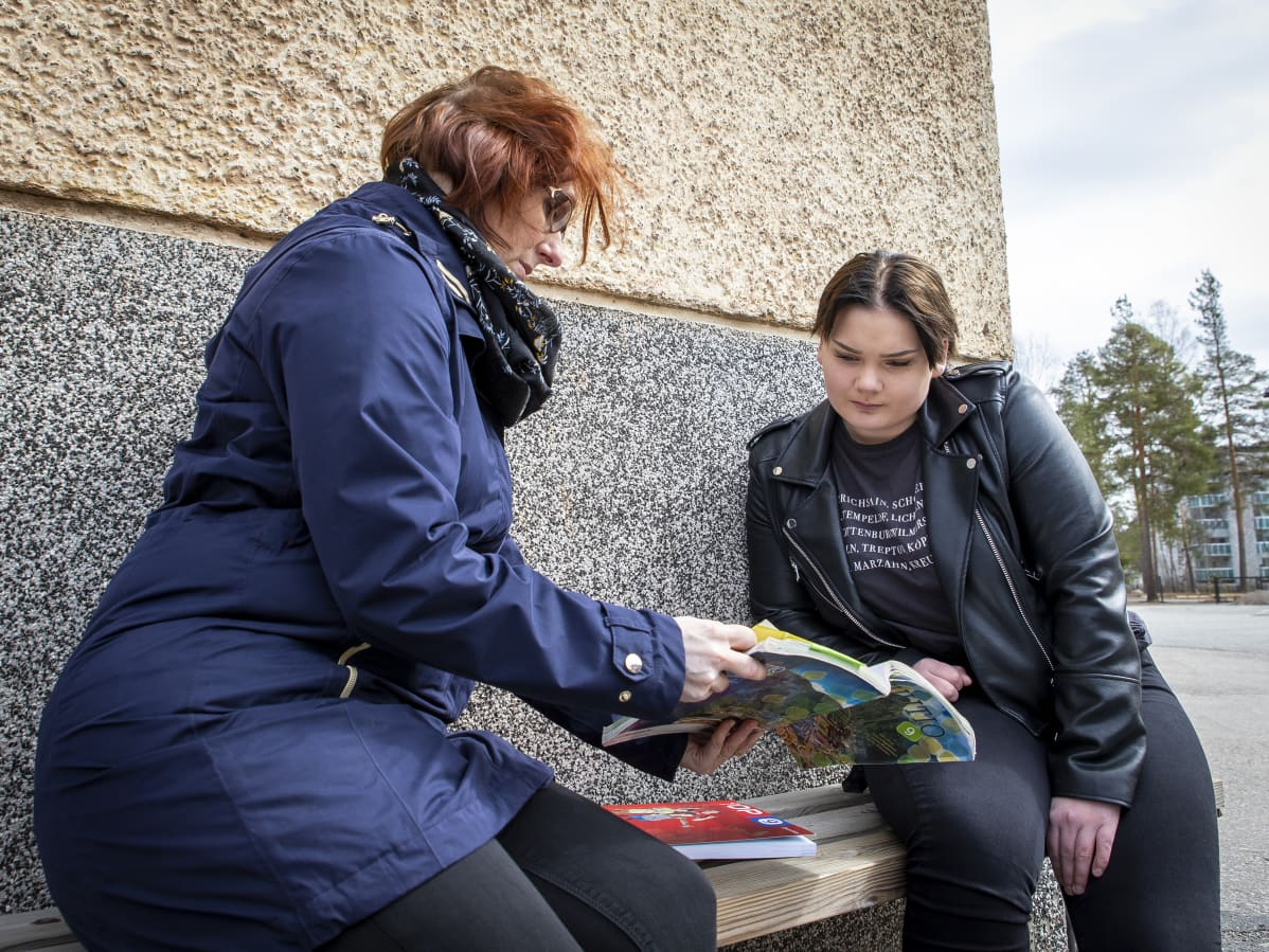 Opettaja Mira Lempinen katselee koulukirjaa Jessica Kaatisen kanssa.