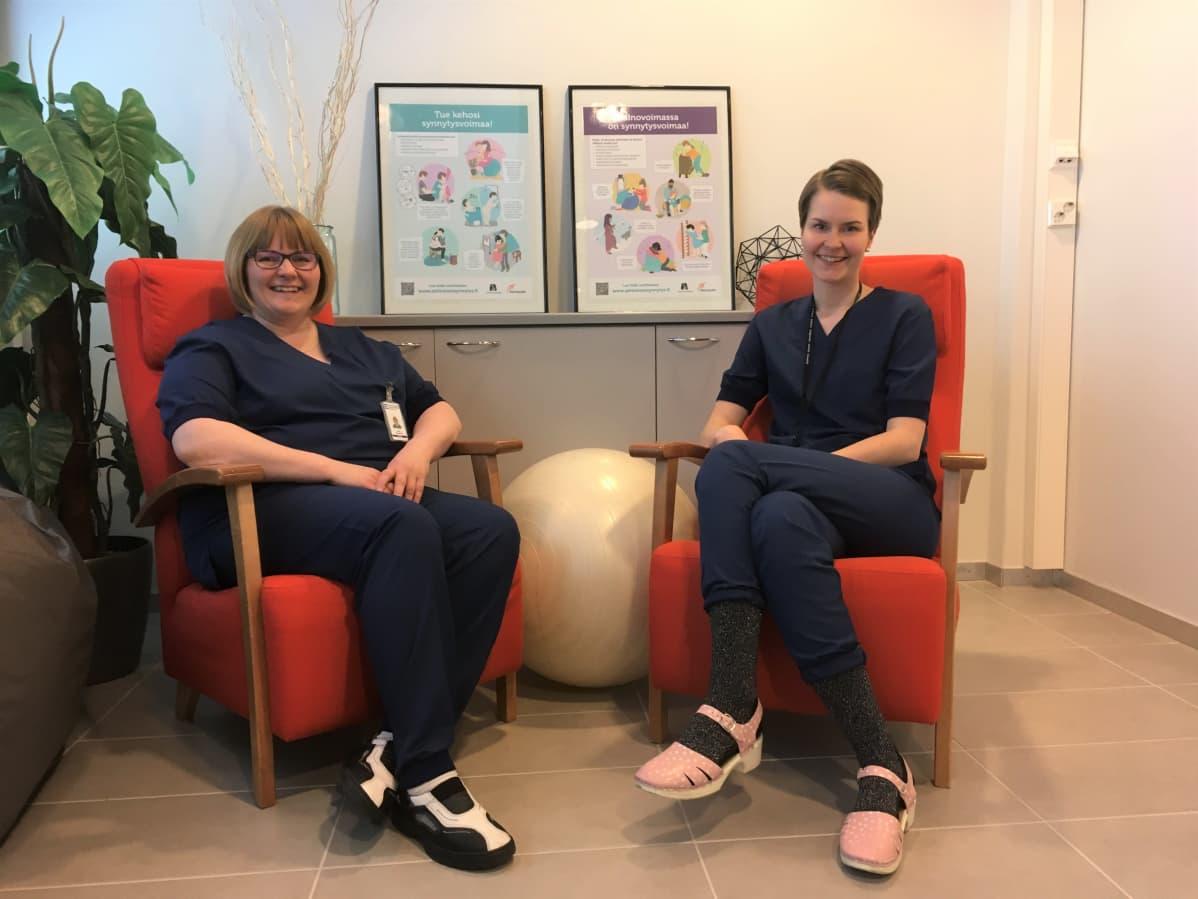 Kätilöt Jaana Loukasmäki ja Vilma Nihti istuvat nojatuoleilla Seinäjoen keskussairaalassa.