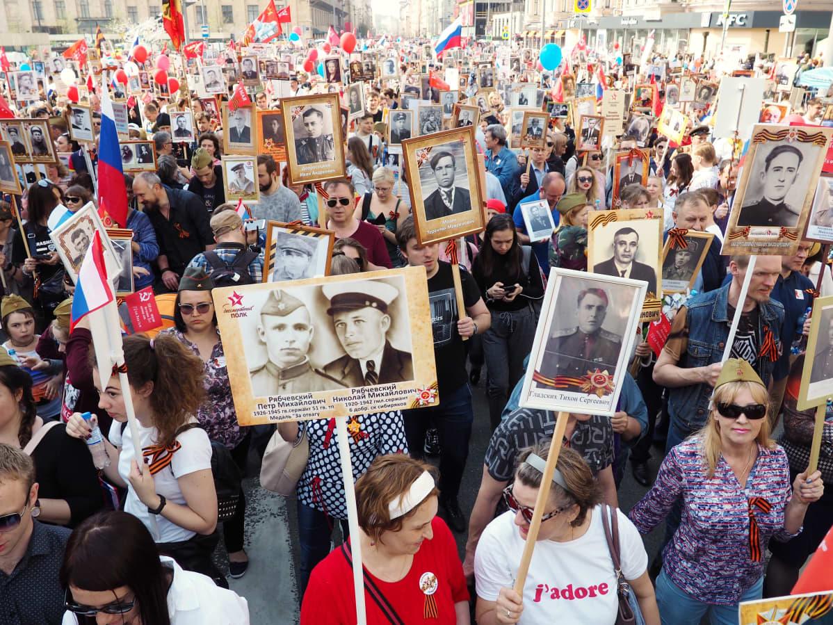 Suuri väkimäärä kulkee kadulla kantaen sotaan osallistuneiden sukulaistensa kuvia.