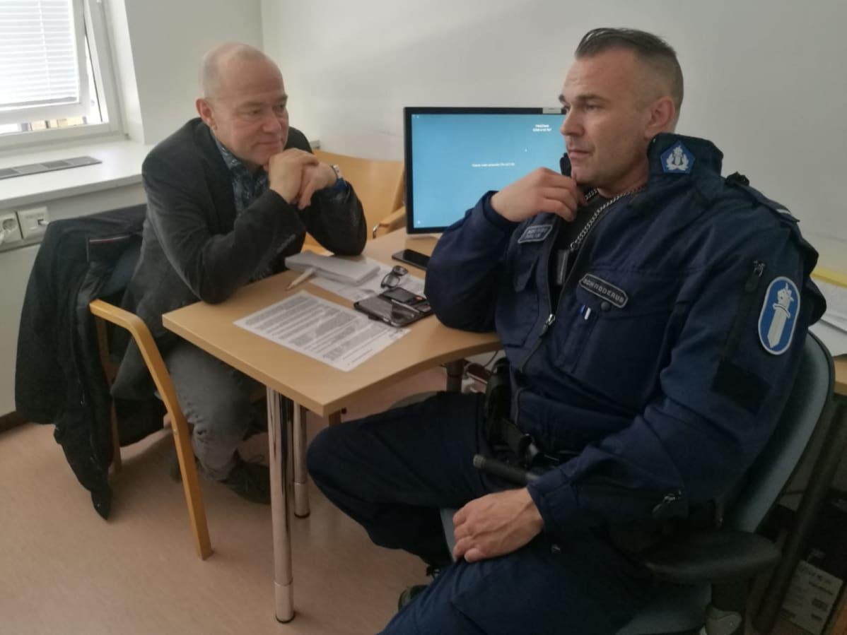 Kaksi miestä istuu keskustelemassa työpöydän äärellä pienessä huoneessa