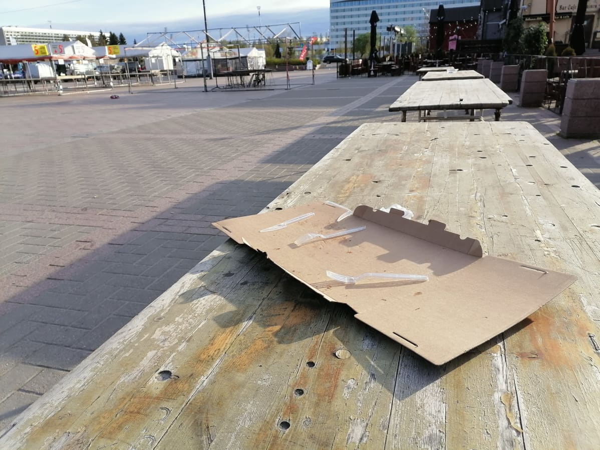 Pahvinen pitsalaatikko on jätetty Oulun torilla sijaitsevalle pöydälle.