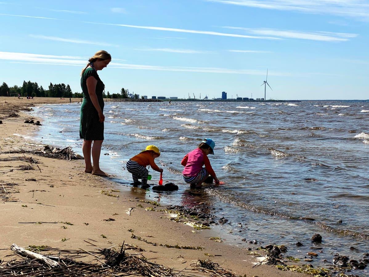 Lapsia leikkimässä rantavedessä aikuisen valvoessa Oulun Nallikarissa.