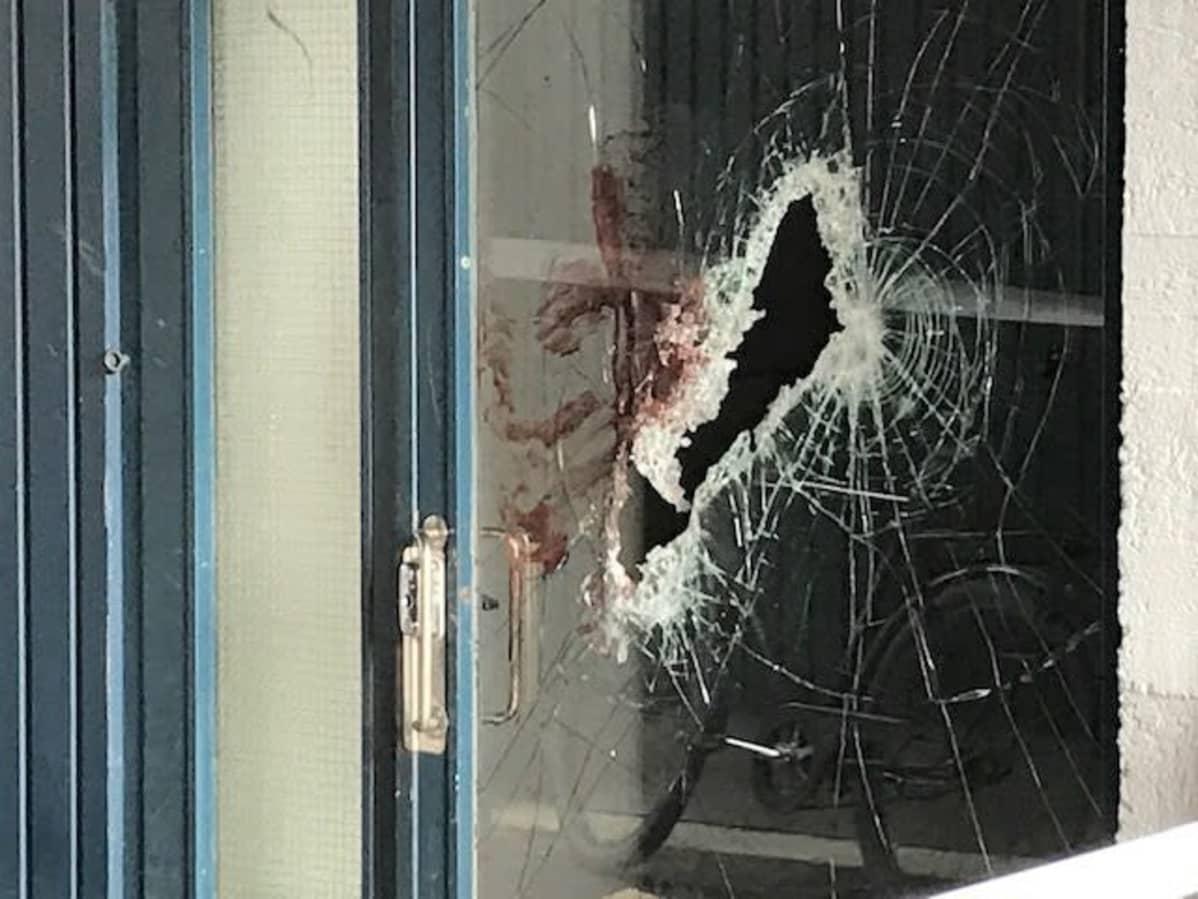 Kuva rikkinäisestä ja verisestä kerrostalon lasiovesta