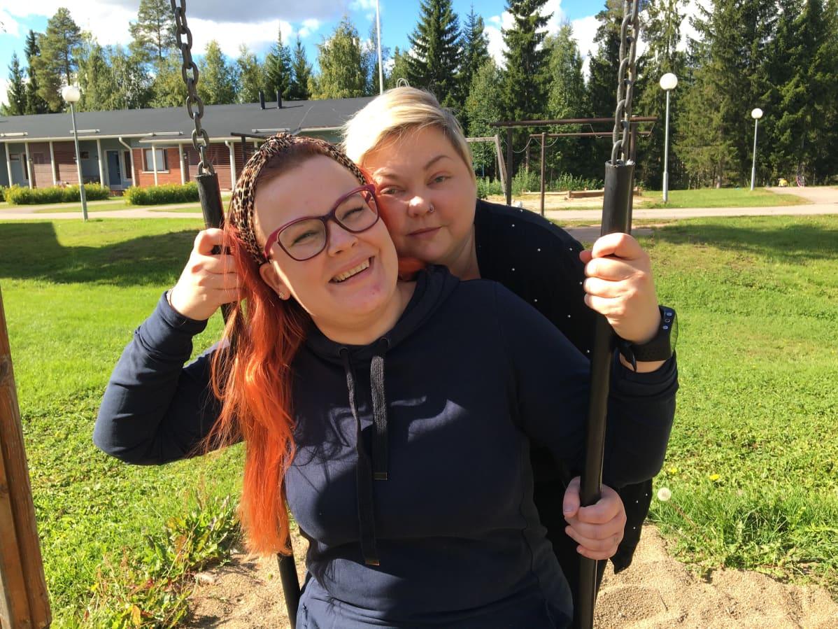 Jenni Hannula istuu keinussa ja Annika Pehkonen seisoo hänen vierellään.