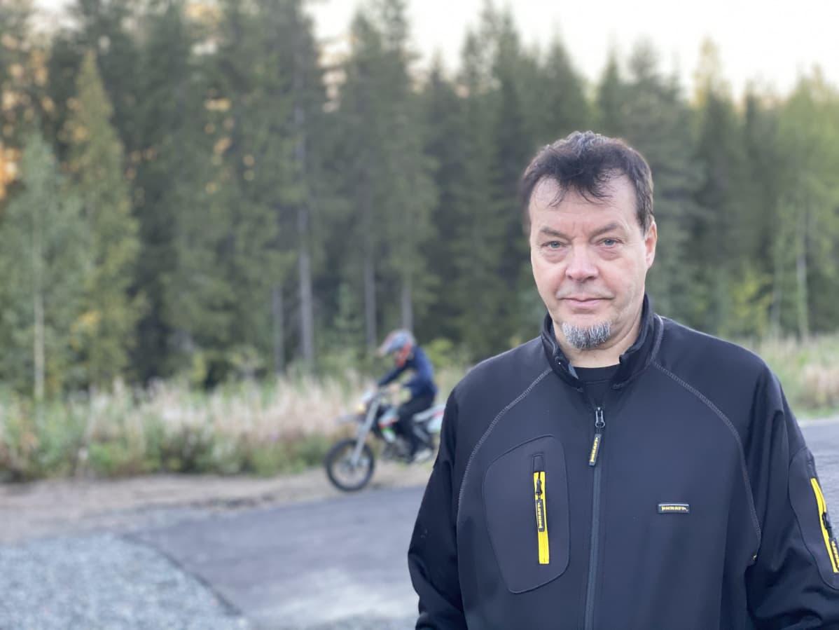 Tiitus Lahti seisoo mopoalueella, Taustalla poika ajaa mopolla.