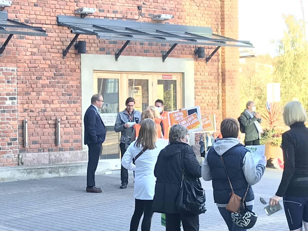 Kaupunginjohtaja Pekka Timonen ja Päijät-Hämeen Ateriapalvelujen sekä JHL:n mielenosoittajia Sibeliustalon edustalla 5.10.2020.
