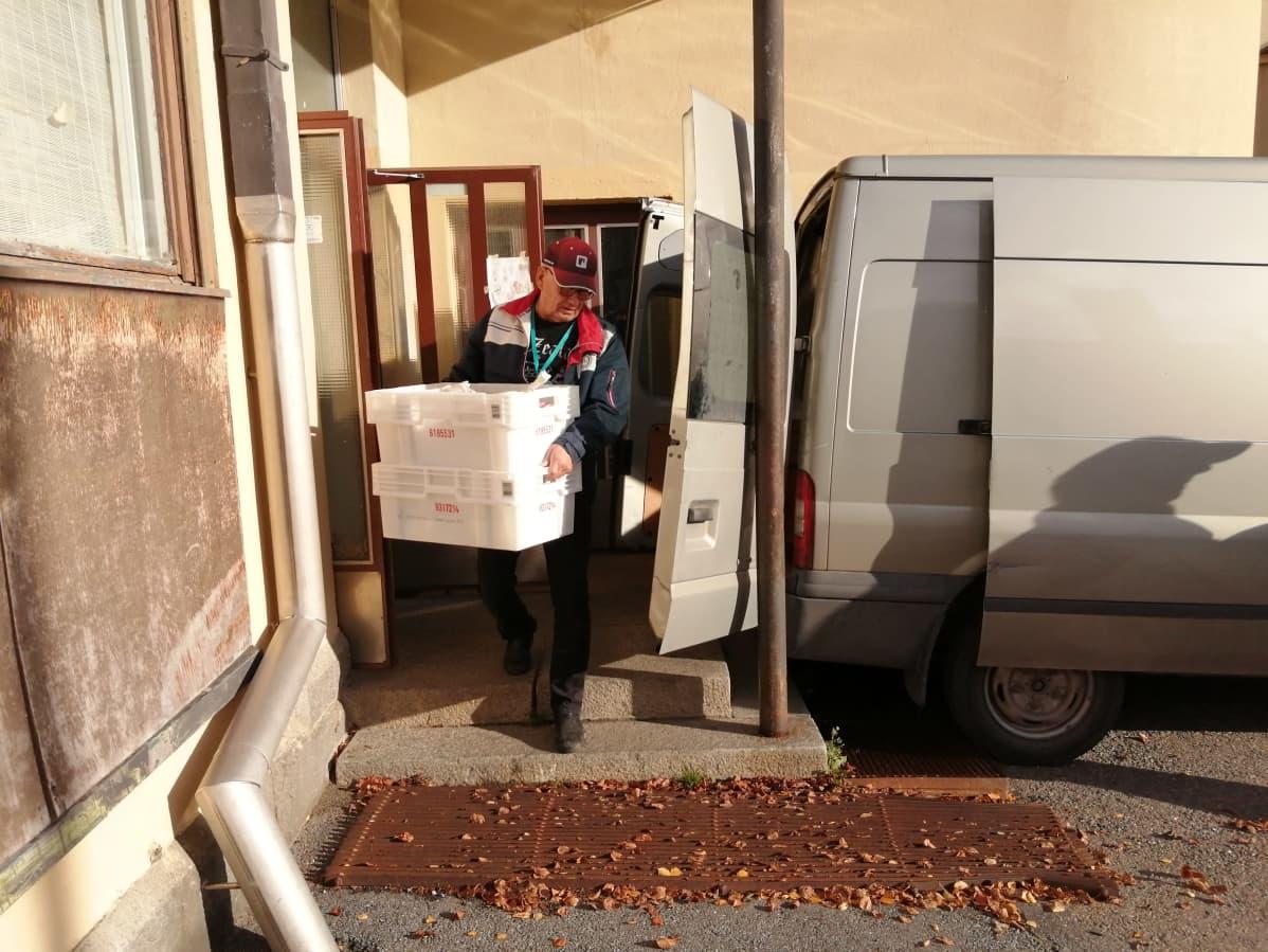 Vaasan ruoka-apuyhdistys pakkaa ruokaa autoihin joilla se kuljetetaan jakelupisteille.