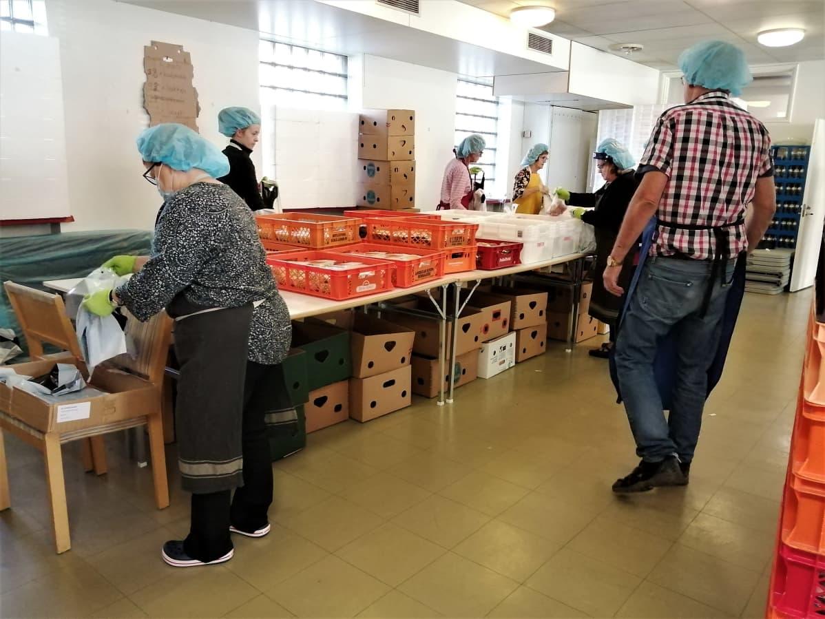 Vaasan ruoka-apuyhdistys pakkaa ruokaa kasseihin liukuhihnamaisesti uusissa tiloissa.
