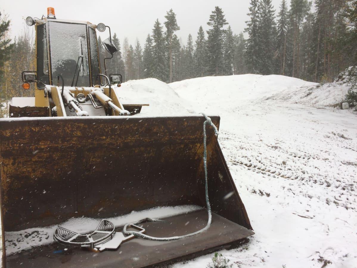 Kaivinkone seisoo paikallaan ohuessa lumessa.