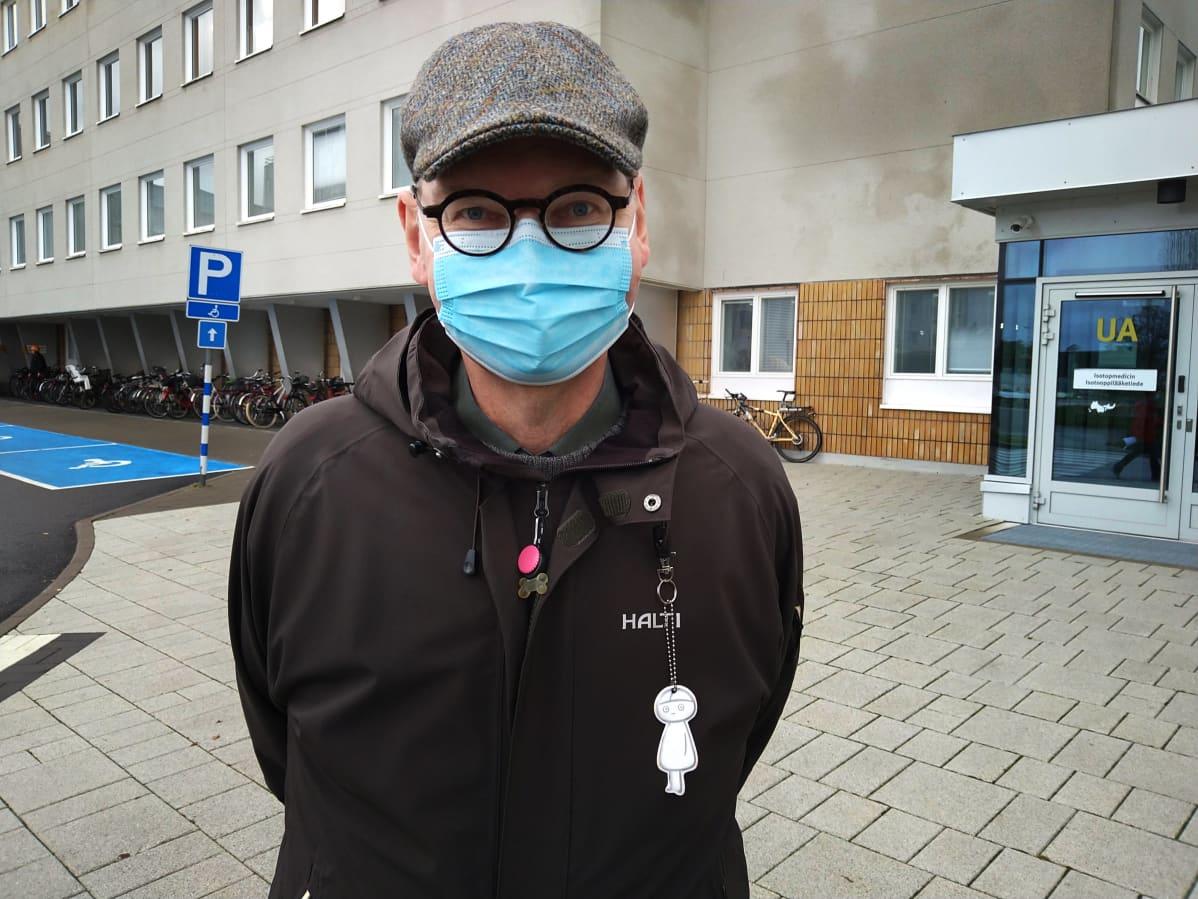 Vaasan johtava ylilääkäri Heikki Kaukoranta harmaassa lippalakissa ja tummassa takissa harmaan sairaalarakennuksen edustalla. Kasvoilla on kertakäyttömaski.