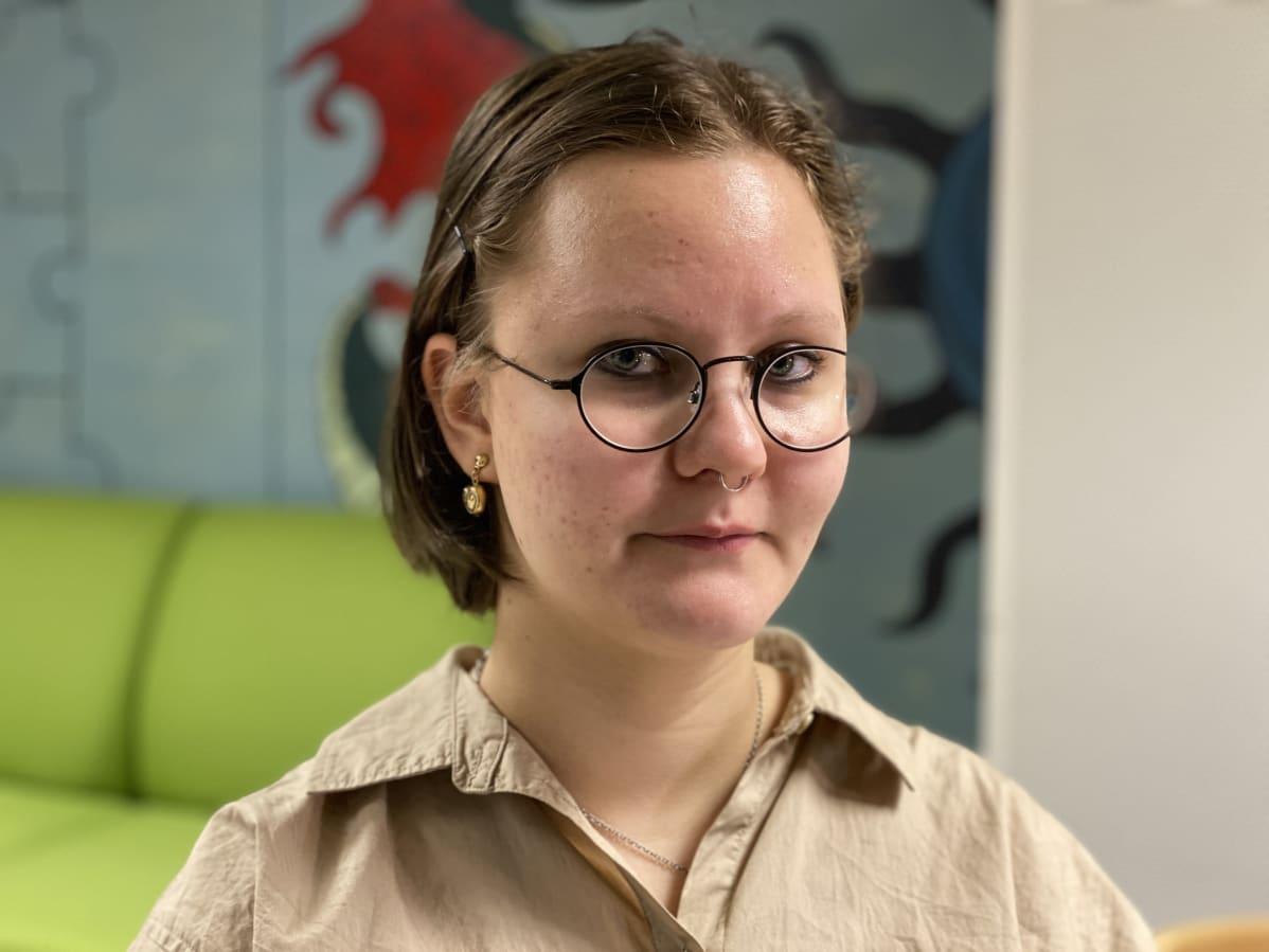 Anetta Kukkonen poseeraa kameralle lukion aulassa.