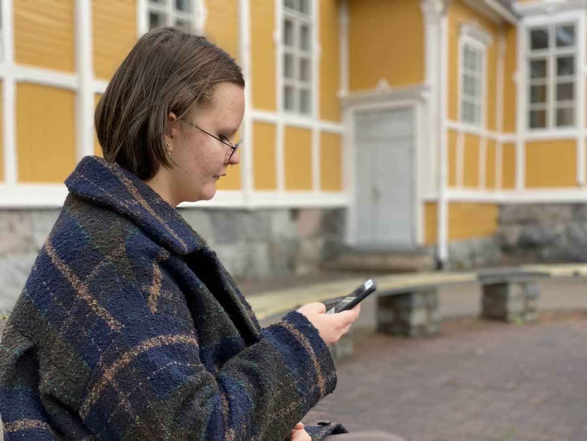 Anetta Kukkonen selaa puhelinta koulun pihalla.