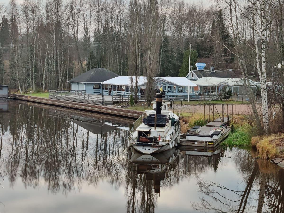 Vene on kesäkahvilarakennuksen laiturissa.