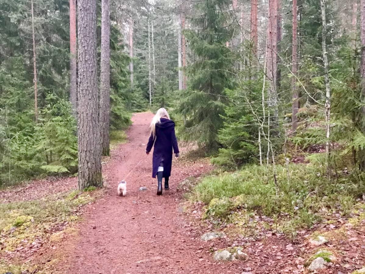 Nainen ja pieni koira kävelevät kuusimetsässä