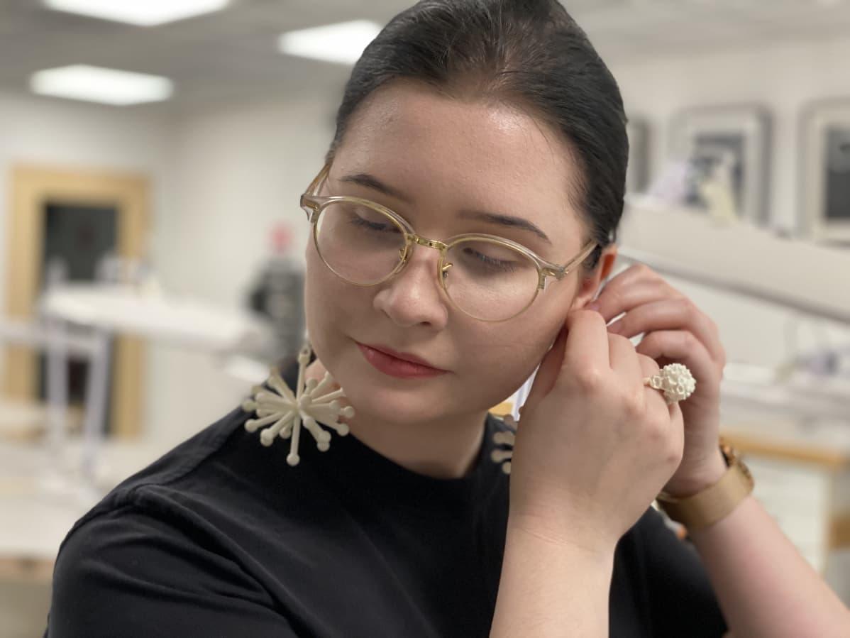 Savonian opiskelija Julia Pirkkalainen laittaa itselleen suunnittelemansa korvakorut.