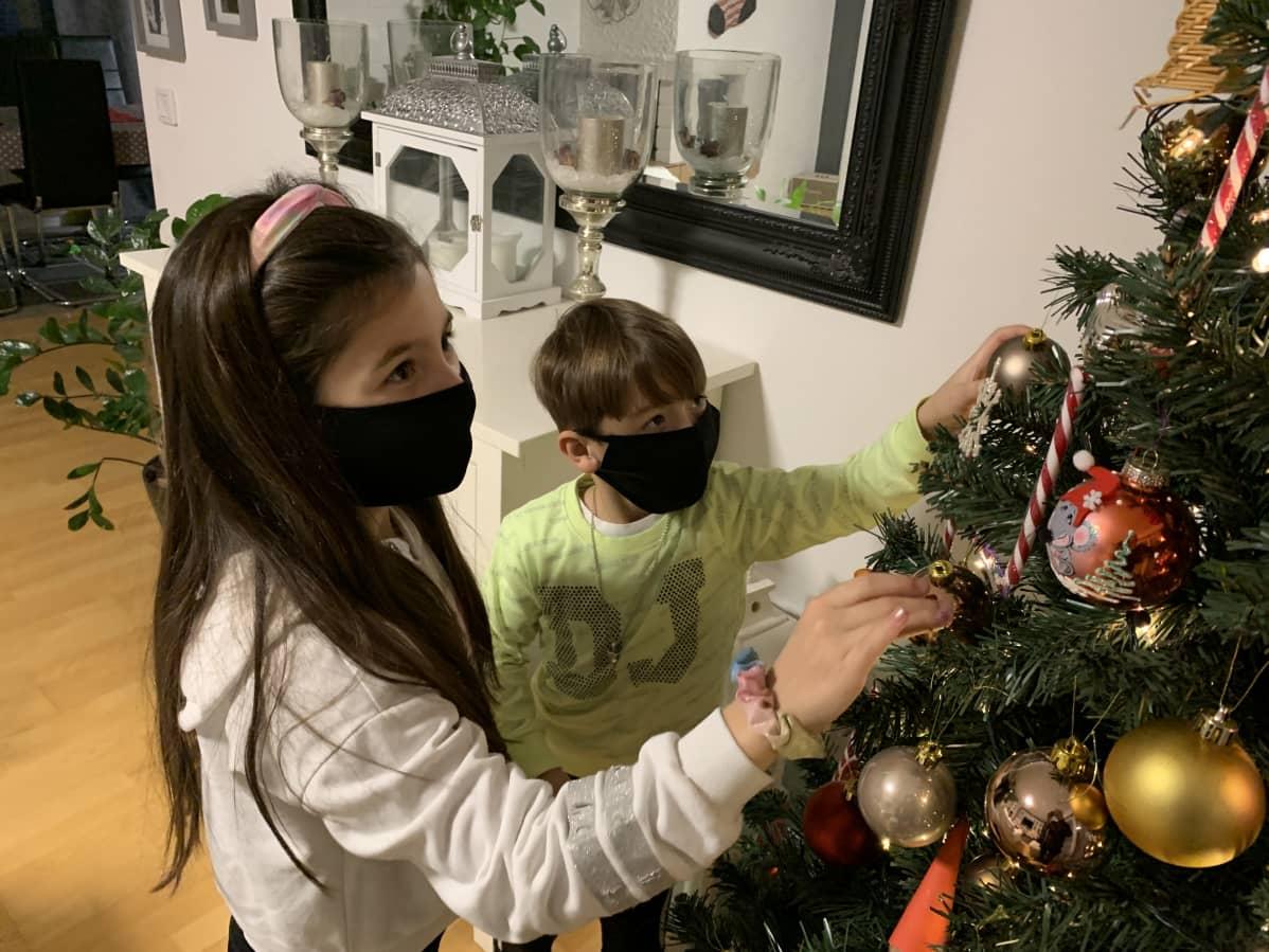 Lapset joulukuusen vieressä