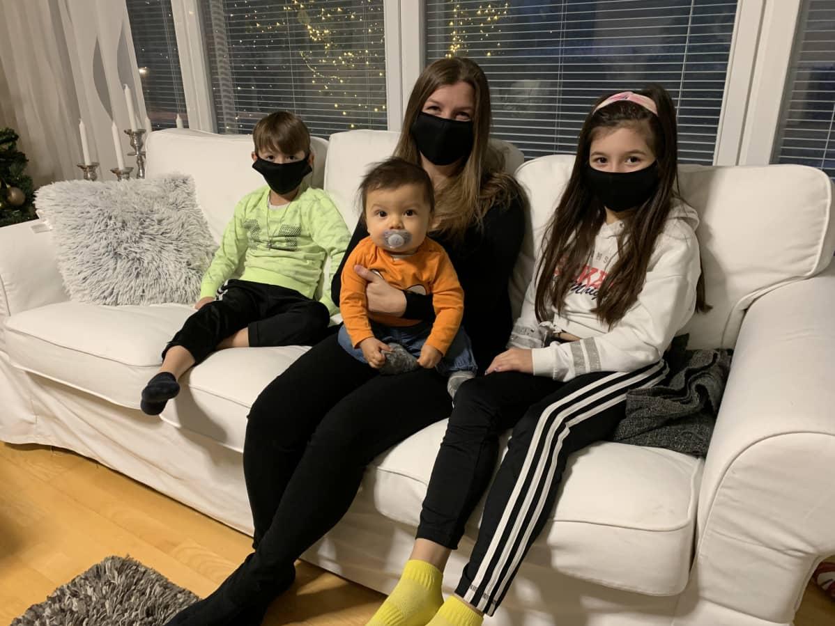 Äiti ja lapset istuvat sohvalla