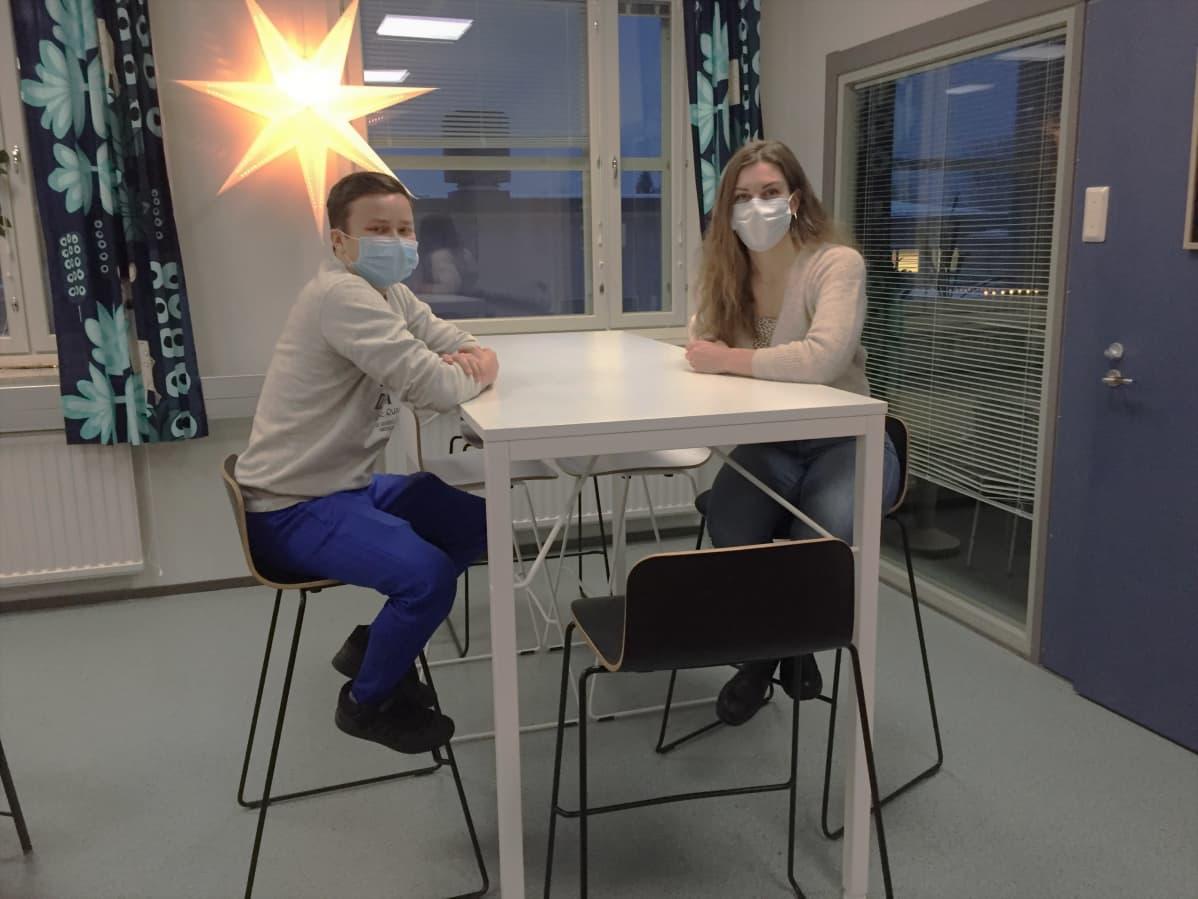 Mikko Repo ja Heidi Selenius istuvat pöydän ääressä.