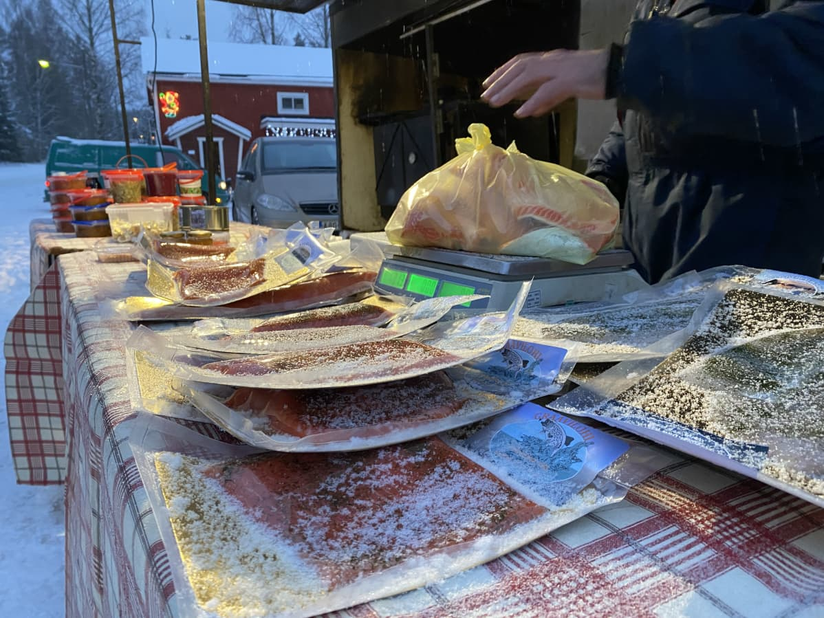Myyntipöydällä on erilaisia lohituotteita pakkauksissa. Myyjä punnitsee pussillista kalaa.