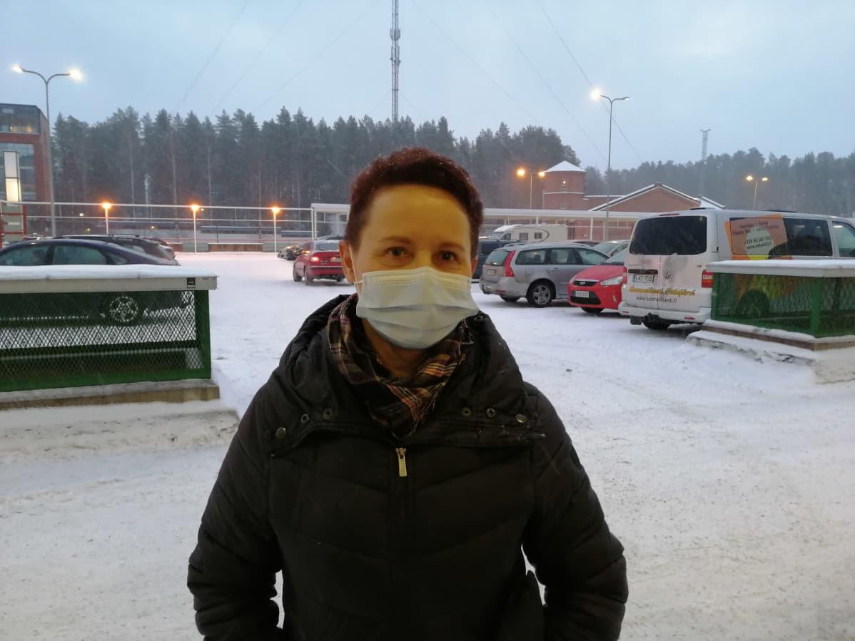 Nainen maski kasvoillaan parkkipaikalla.