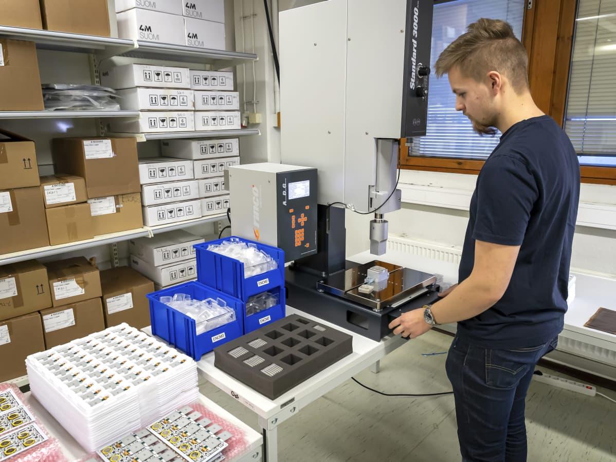 Työntekijä kokoaa loggereita puristimella.
