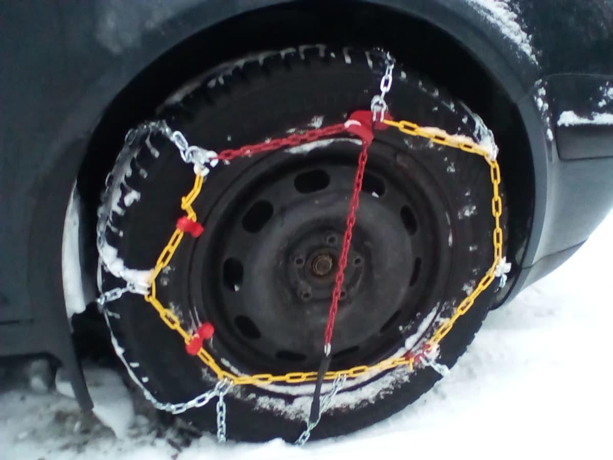 Henkilöauton eturenkaaseen on kiinnitetty pitoa parantavat ketjut.  Pyörään alle jäävältä osalta ketju on kiiltävää, renkaan ulkosivulla myös keltaista ja punaista.