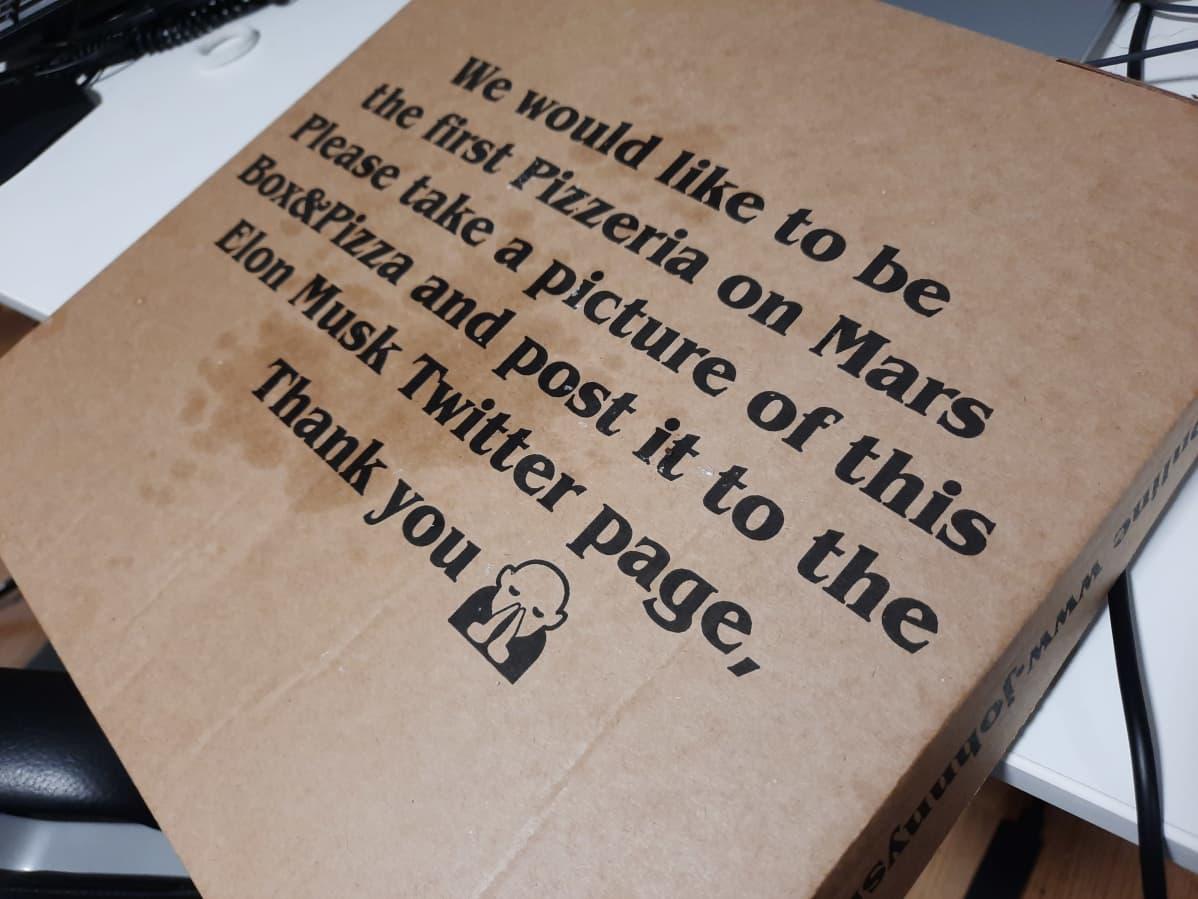 Johnny's Heist pizzalaatikon pohja, jossa lukee englanniksi: Haluamme olla ensimmäinen pizeria Marsissa. Ota kuva tästä tekstistä ja pitsasta. Twiittaa kuvat Elon Muskille.