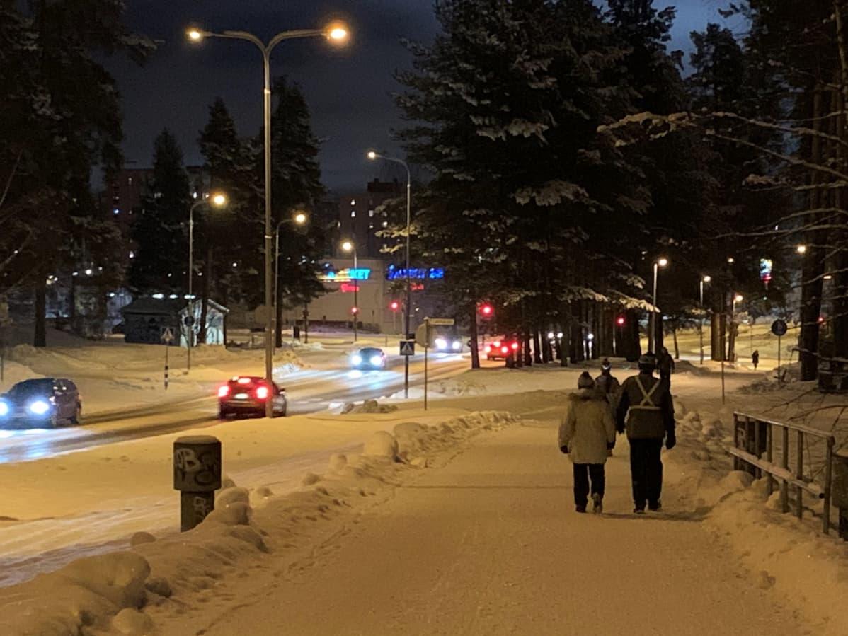Ihmisiä kävelyllä talvisella kevyen liikenteen väylällä