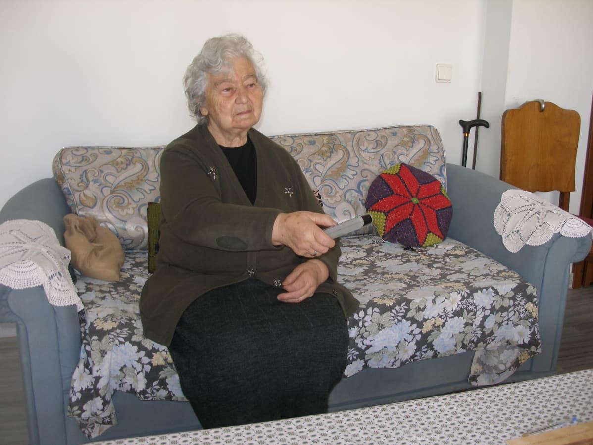 Iäkäs nainen istuu sohvalla katsomassa televisiota.