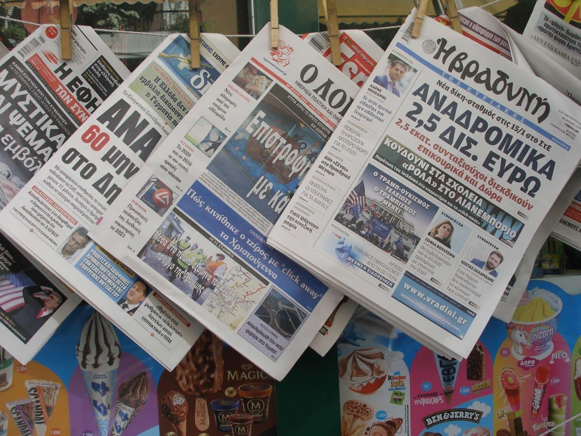 Kreikkalaisia sanomalehtiä roikkuu narulla kioskin edessä.