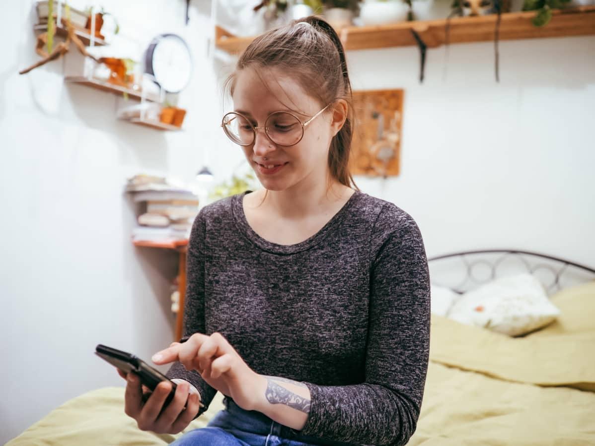 Nainen istuu sängyllä ja selaa puhelintaan.