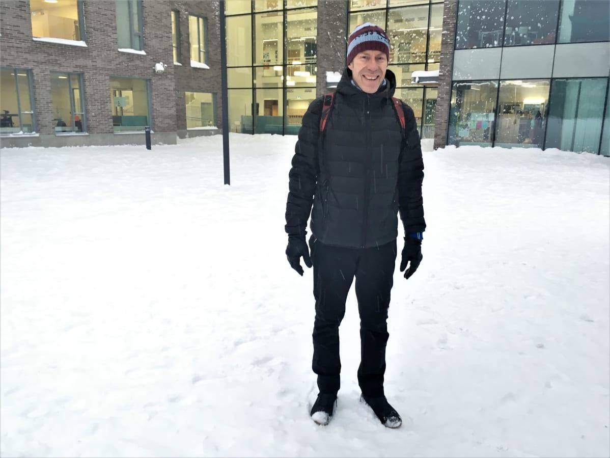 Opettaja Petri Kotro koulun edustalla seisomassa.