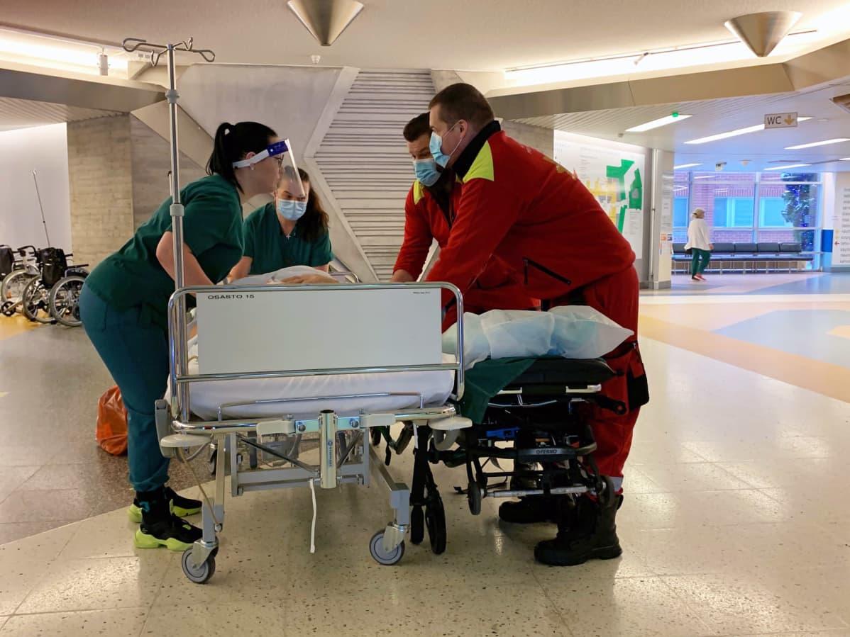 Henkilökunta kuljettaa potilasta sairaalan käytävällä.