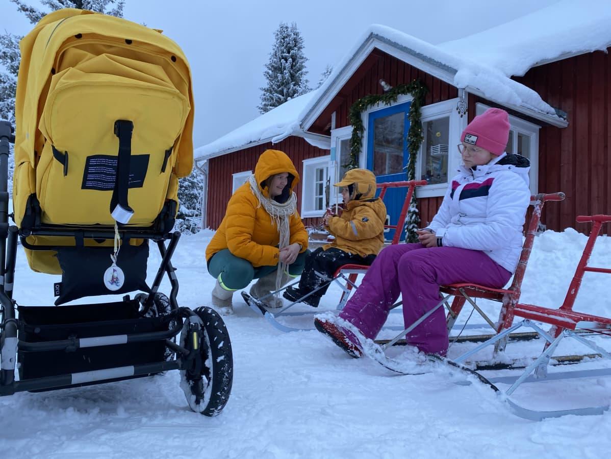 Keltaiset lastenvaunut, Anne Jäntti kyykyssä Iipon ja Millin vieressä, jotka istuvat potkureissa.