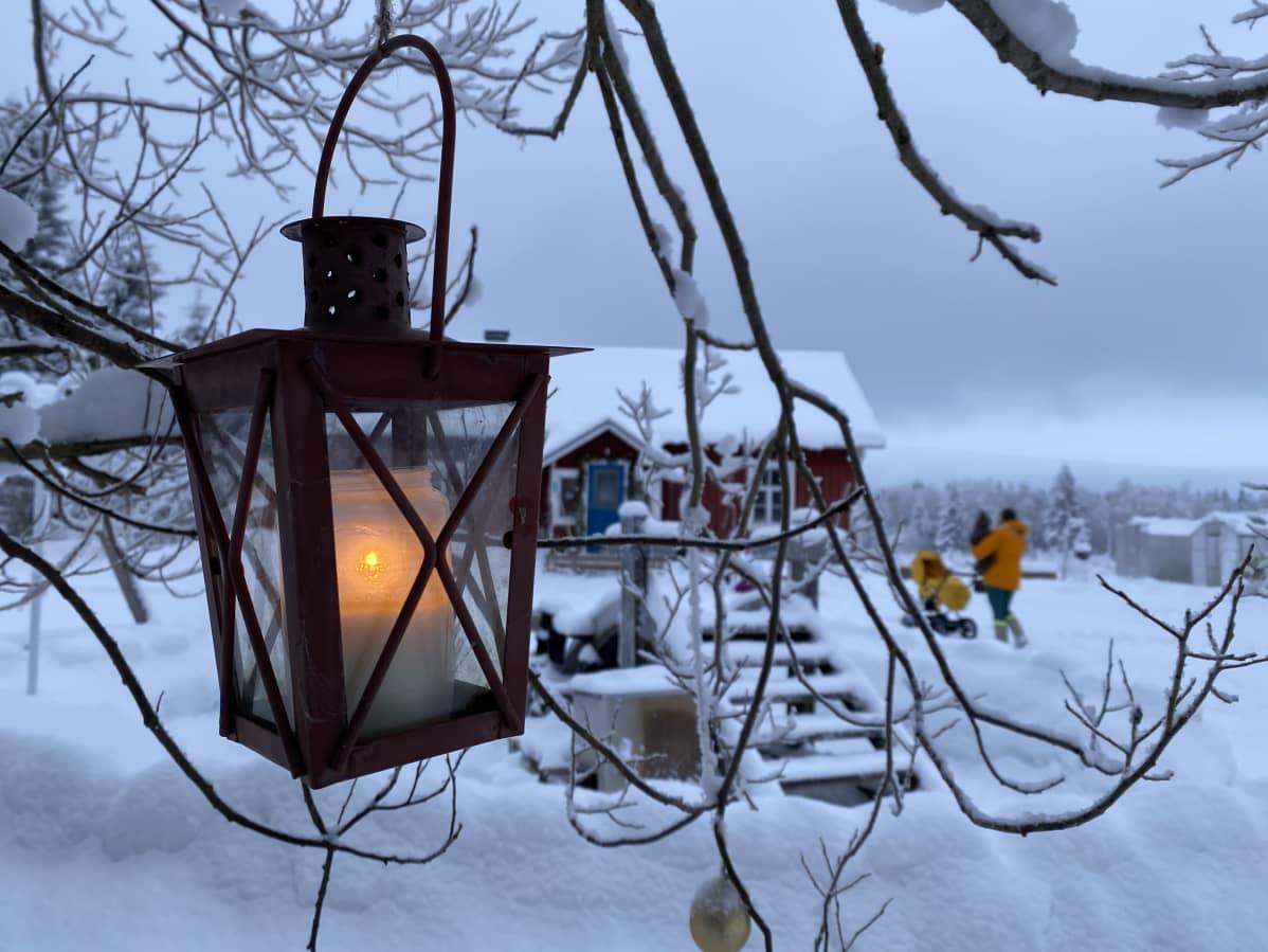Etualalla lyhty, jossa palaa kynttilä. Se roikkuu puun oksalla. Taustalla punainen hirsitalo. Anne ja lapset ovat kävelemässä kohti taloa.