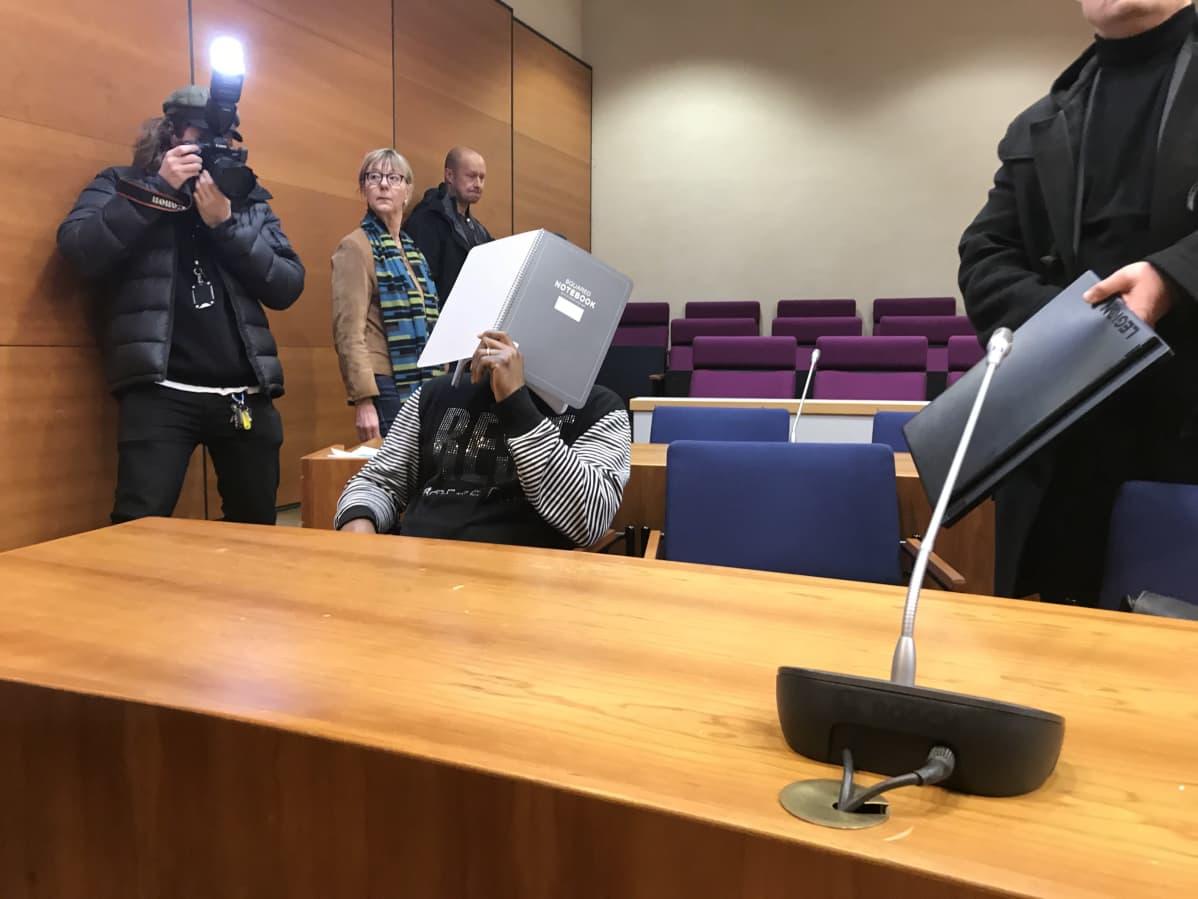 En person täcker sitt ansikte i en rättegångssal.