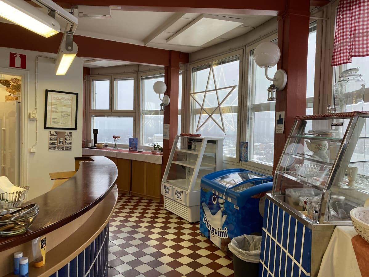 Sisäkuva kahvilasta vesitornin ylimmässä kerroksessa, kahvilan tiski ja jäätelöpakasti. Ikkunoista näkymät Heinolan kaupungin yli.