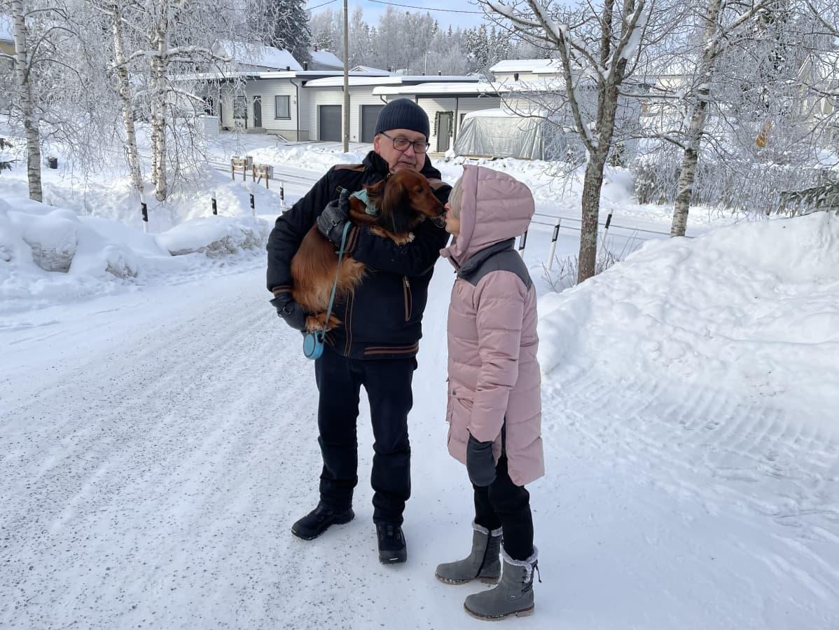 Kaksi ihmistä talvisessa maisemassa pihalla. Miehellä on sylissään koira, nainen antaa koiralle pusun.