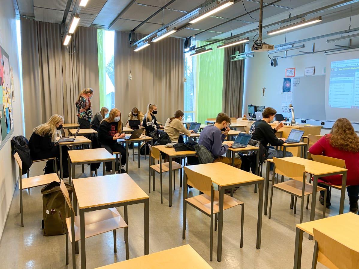 Opiskelijat istuvat luokkahuoneessa, maskit kasvoillaan.