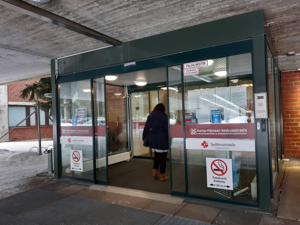 Ihminen kävelee sairaalan ovesta sisään.